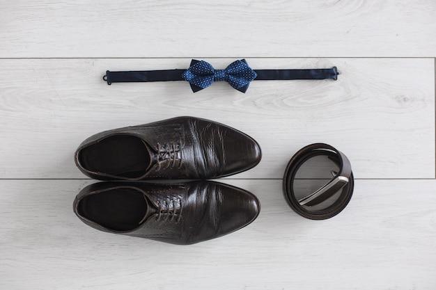 Темно-коричневые мужские туфли и ремешок на белом фоне