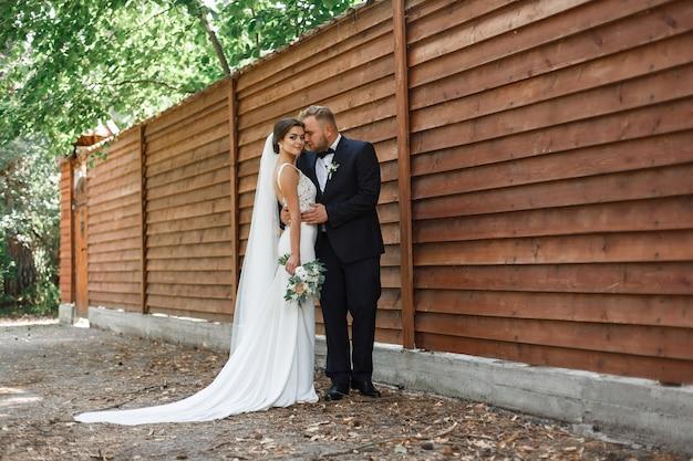 木製の背景に幸せな笑みを浮かべて花嫁の肖像画。結婚式。春に屋外の結婚式の日に感情的な新郎新婦。外のロマンチックな瞬間を楽しむ若い結婚式のカップル。