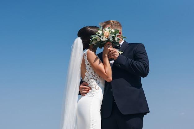 新郎新婦が花束の後ろに隠れてキスします。新郎は屋外で花嫁を情熱的に抱きしめます。結婚式。晴れた日の春に屋外の結婚式の日に新婚夫婦。