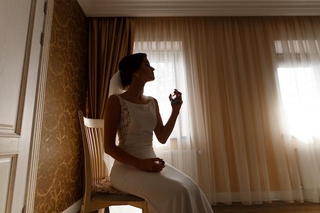 Стильная женщина в белом платье спрей нежный парфюм в помещении
