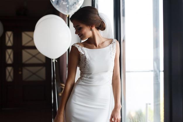 Красивая улыбающаяся невеста в модном свадебном платье в помещении возле окна