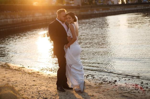 Красивые молодые свадьбы пара стоит на берегу моря
