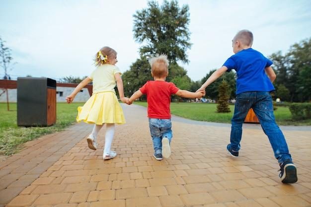 晴れた日に夏に公園を歩いて女の子と小さな男の子。小さな友達は屋外で手をつないでいます。幸せな子供時代。野外を歩いている感情的な子供。自然で遊ぶ兄と妹