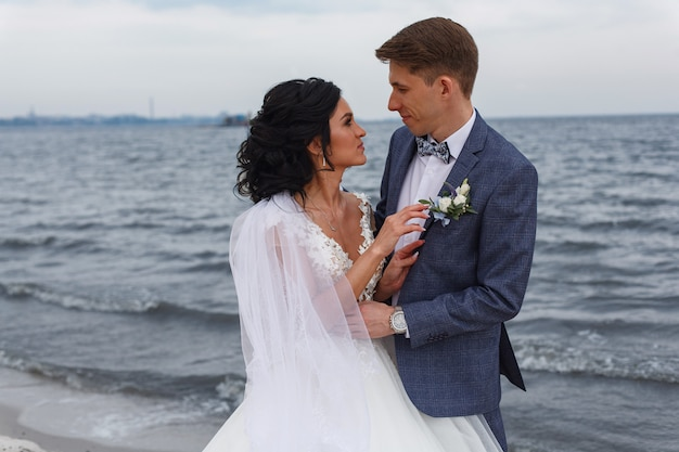 川のビーチで屋外の結婚式の日に新郎新婦の結婚式のカップルの笑顔