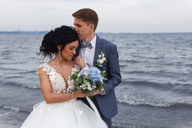 川のビーチで屋外の結婚式の日に新郎新婦の美しい結婚式のカップル