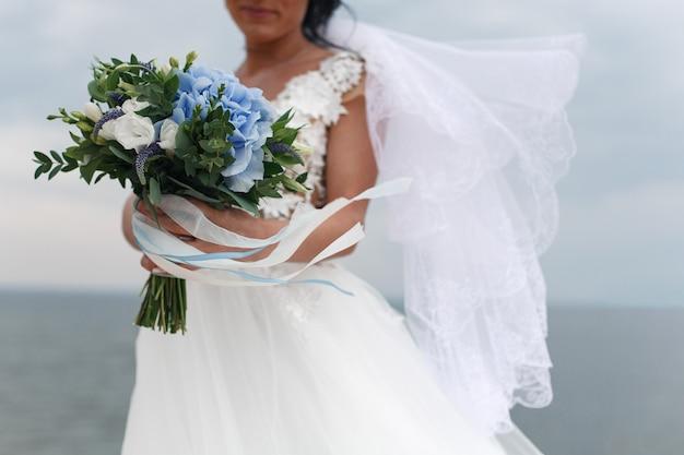 Портрет красивые улыбающиеся невесты с нежным свадебным букетом в руках на открытом воздухе на фоне неба и песка