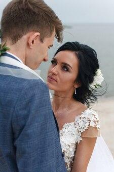 Гулять по песку вдоль реки. невеста в белом платье сидит на песке