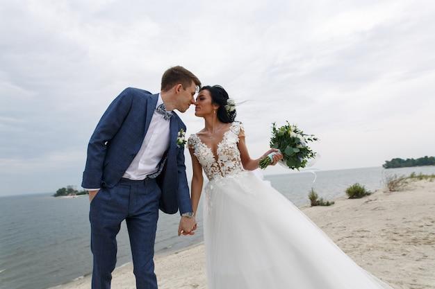 ビーチで屋外の結婚式の日に新郎新婦の美しい幸せな結婚式のカップル