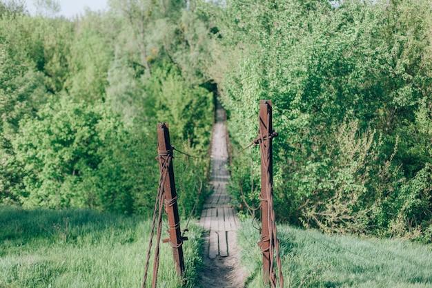 Висящий старый деревянный мост. старый висячий пешеходный мост через речку