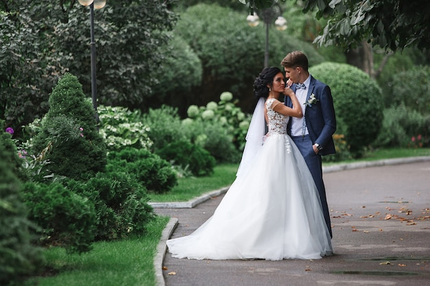 Портрет красивой свадьбы пара на прогулке в зеленом парке