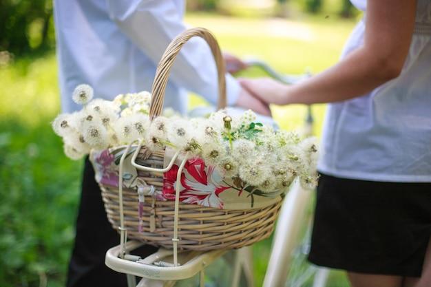 タンポポと自転車で花を持つバスケット自転車で屋外の男とガールフレンドのロマンチックな散歩。