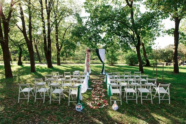 結婚式のアーチの装飾と緑の公園の椅子。晴れた日に屋外で結婚式を祝います。緑の芝生の上の美しい結婚式。