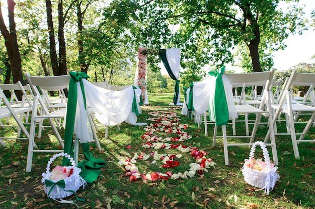 結婚式のアーチの装飾と緑の芝生の上の椅子。お祝いの場所のお祝い。春の緑豊かな公園で美しい結婚式。
