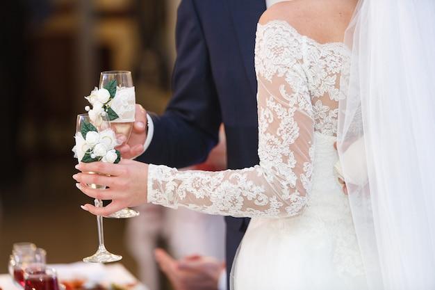 結婚式の日に装飾されたワイングラスを持つカップル