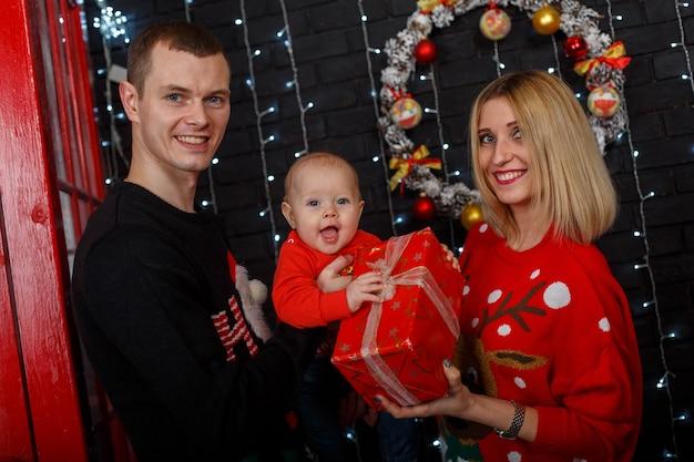母と父と赤いセーターの面白い小さな赤ちゃん。メリークリスマスの家族写真。
