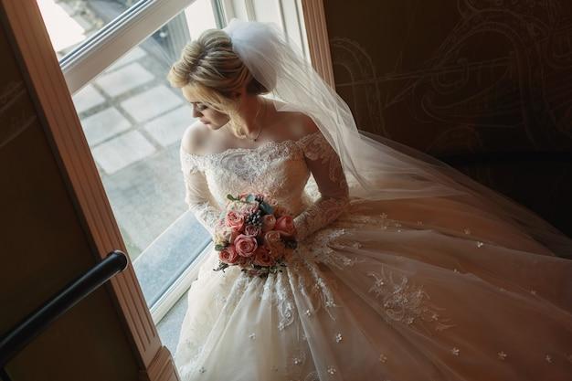 屋内ピンクのバラのブライダルブーケとかわいい花嫁の肖像画。窓の近くの豪華なドレスと長いベールでかなり幸せな花嫁。花の花束を保持している美しいネックラインを持つ若い花嫁。