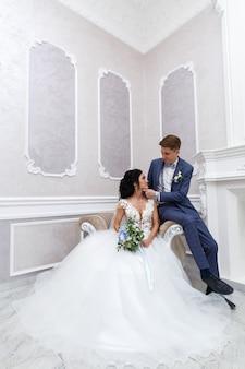 Молодожены нежно смотрят друг на друга. портрет невесты и жениха обниматься в свадебной церемонии в стильном интерьере. счастливый день пропалывания