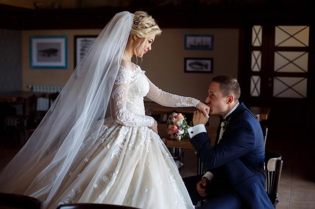 幸せな新婚夫婦の肖像画。新郎は、スタイリッシュなインテリアで屋内の花嫁の手にキスします。花嫁はそっとお互いを見ます。結婚式の日。ロマンチックな瞬間