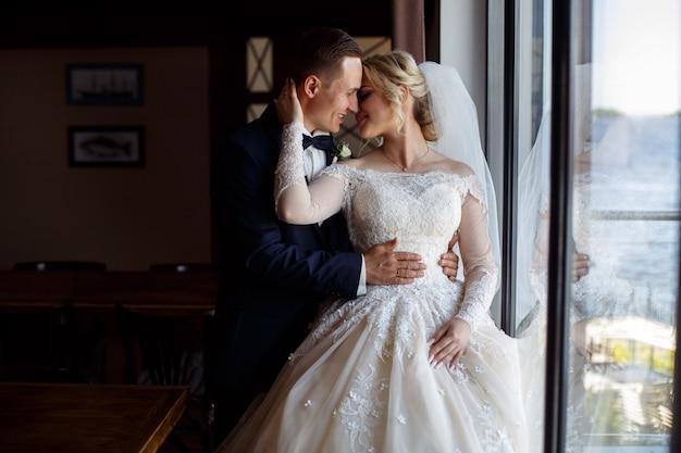 Жених и невеста целуются нежно. эмоциональное фото влюбленной пары в день свадьбы. улыбающиеся молодожены возле большого окна. свадебная фотография.