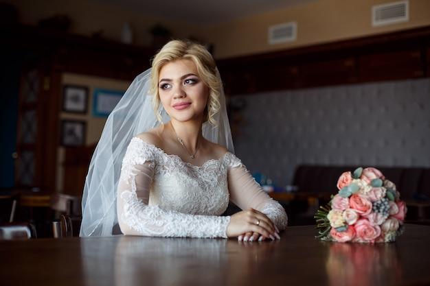 屋内のバラの花束とかわいい花嫁の肖像画。ピンクの花でスタイリッシュなインテリアの豪華なドレスで笑顔の幸せな花嫁。