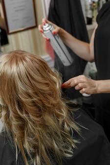美容院でのヘアスタイリングのプロセス。ヘアマスター。クライアントと働くプロの美容師。手にヘアスプレーで美容院をクローズアップ。