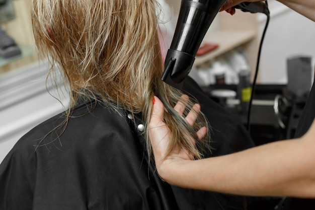 ヘアスタイリングプロセスをクローズアップ。ヘアマスター。美容院。職場での美容院。手でドライヤー付き美容院をクローズアップ。