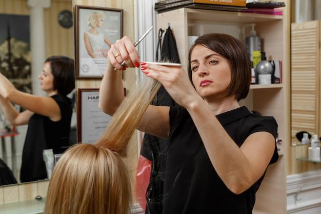 散髪のプロセス。ハサミと櫛の手で美容院をクローズアップ。ヘアマスター。美容師向けのコース。