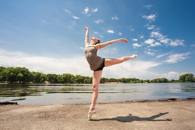 屋外のポイントでバレエダンサーの肖像画。魅力的なバレリーナダンス。自然の中での体操。バレリーナが立ち、ツバメのポーズを実行します