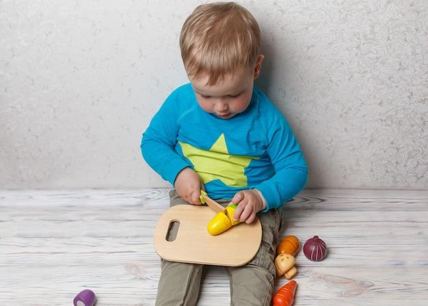 面白い子がシェフで遊ぶ。笑顔の男の子は木製の野菜をカットします。面白い安全な開発の子供のゲームをクローズアップ。小さな男の子は、プラスチックのおもちゃのキッチンで遊ぶ。