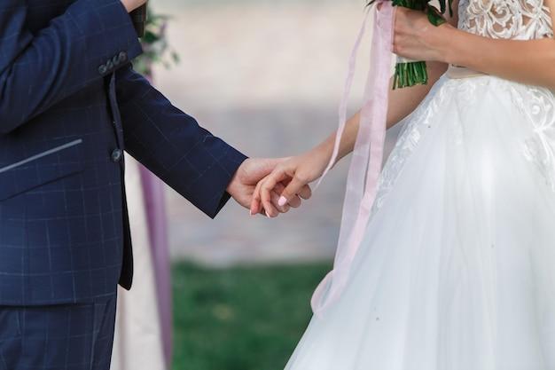 結婚式の新郎新婦。屋外手を取り合って幸せな新婚夫婦をクローズアップ。結婚式のコンセプト。結婚式の日。美しいちょうど結婚されていたカップル