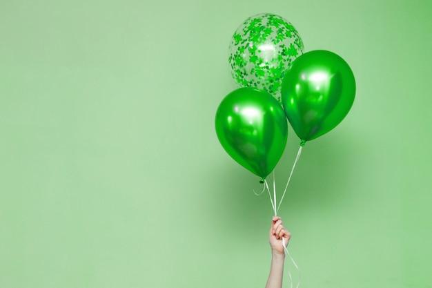 Рука три яркие красочные воздушные шары в помещении.