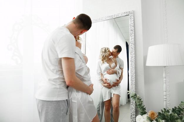 Муж нежно целует и обнимает беременную жену в стильном интерьере. нежные объятия будущих родителей в спальне перед зеркалом. счастливая семья ждет ребенка.