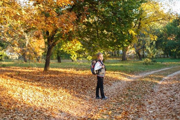 秋に屋外のバッグと白いシャツで感情的な学校少年。秋の公園を歩いてかわいい学校少年。小学生はバックパックで学校に行きます。外で笑顔の生徒
