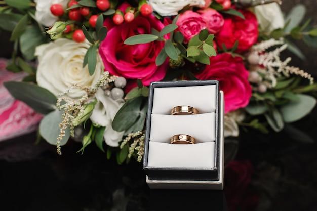 ウェディングブライダルブーケ。ボックスの結婚指輪。刻まれたホワイトゴールドの美しい婚約指輪をクローズアップ。結婚式の日。結婚式の詳細。