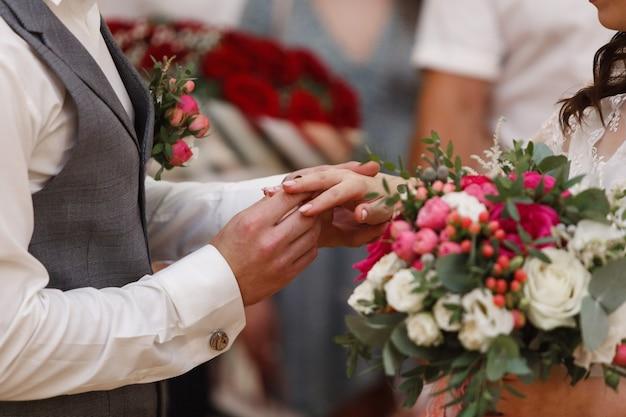 結婚式をクローズアップ。新婚夫婦は金の結婚指輪を交換します。ちょうど夫婦。彼は彼女に結婚指輪を置いた。新郎は花嫁のためのリングを置く
