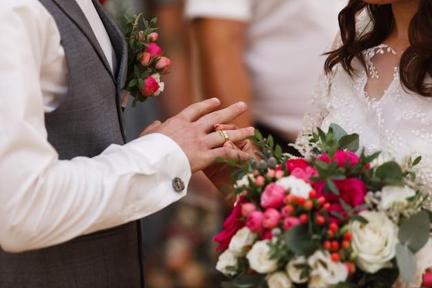 結婚式がクローズアップ。カップルは金の結婚指輪を交換します。幸せなちょうど結婚されていたカップル。彼女は彼のために結婚指輪を置きました。花嫁は、新郎に指輪を置きます。