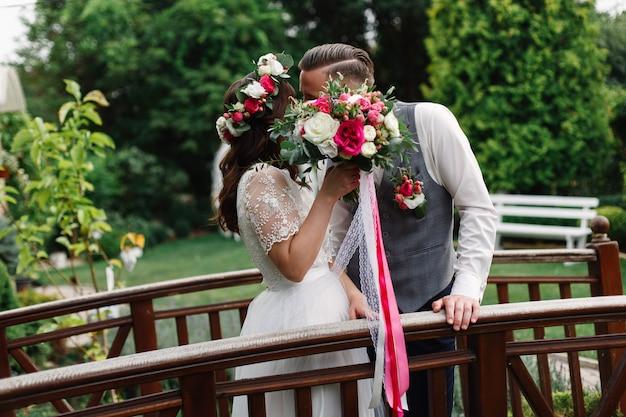 春の結婚式の日。新婚夫婦は屋外の結婚式でキスします。赤い花束と花嫁を優しく抱き締めるボタンホールと新郎。結婚式のロマンチックな瞬間をクローズアップ