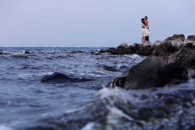 岩の多いビーチで美しい結婚式のカップル。日没で手をつないで、屋外を抱いてスニーカーでスタイリッシュな新婚夫婦。海岸に立っている新郎新婦。自然に恵まれた日。ロマンチックなデート