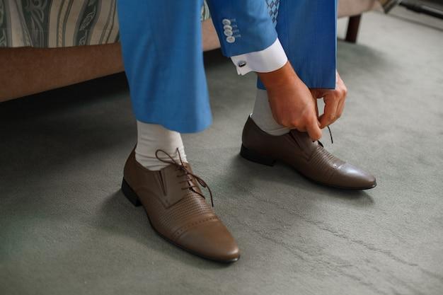 新郎は茶色の靴のひもをクローズアップで縛ら。ビジネスの男性は、朝ホテルの部屋で屋内の靴をぶら下げています。手と革の男性の靴のペア。新郎の会議。