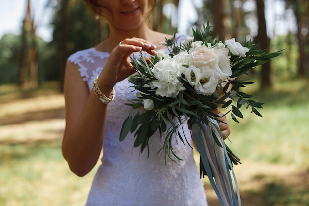 Портрет улыбающейся невесты на прогулке на свежем воздухе. молодая женщина с букетом цветов весной в солнечный день. красивый свадебный букет из белых и розовых цветов. детали свадьбы