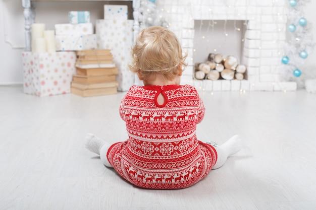 クリスマスのレンガの暖炉の近くの赤いドレスを着た少女の肖像画は家に飾られています。おもちゃとギフトボックスが付いている屋内のクリスマス休暇