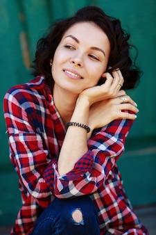 緑の壁に巻き毛の若い女性の肖像画。ジーンズと街の赤いシャツで笑顔と感情的な女の子。晴れた日の屋外でかわいい若い女性
