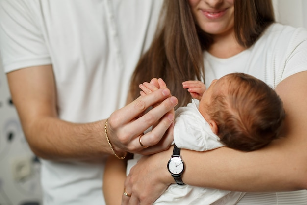 お父さんとお母さんの腕の中で生まれたばかりの赤ちゃん。若い親の腕の中で新生児がクローズアップ。
