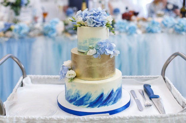 トレイに花で飾られた美しいウェディングケーキをクローズアップ。フォークとナイフで白と青の階層型ウェディングケーキ
