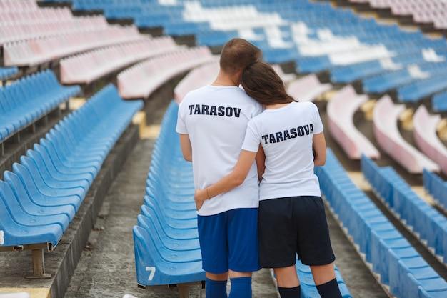 感情的な男と女がスタジアムでキスします。スポーツスタジアムでハグスタイリッシュな若いカップル