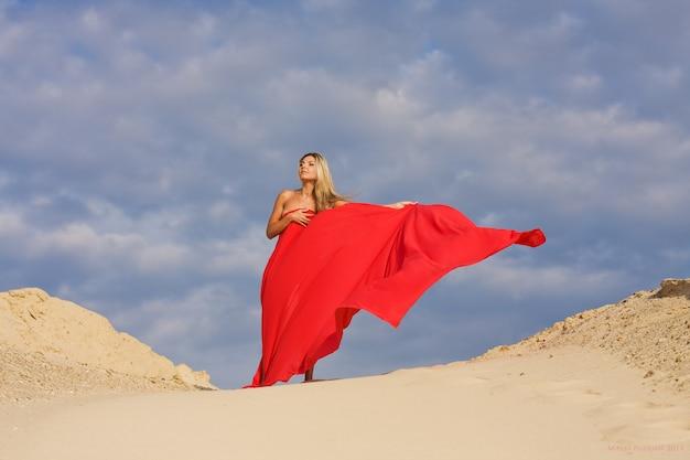 屋外の砂の丘の上の長い赤いドレスの魅力的な若い女性。長いドレスを着た美しい女性は、暑い晴れた日に砂丘に沿って歩きます。