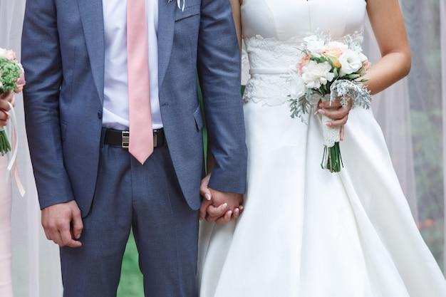 美しいブーケと新郎新婦の結婚式。ちょうど夫婦。屋外手を取り合って幸せな新婚夫婦をクローズアップ。結婚式の日。