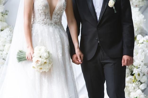 美しいブーケと新郎新婦の結婚式。ちょうど夫婦。手を繋いでいる幸せな新婚夫婦をクローズアップ。結婚式の日。