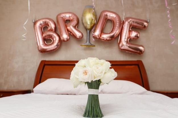 ホテルの部屋で白いバラのスタイリッシュな花束をクローズアップ。碑文「花嫁」と寝室のブライダルブーケ