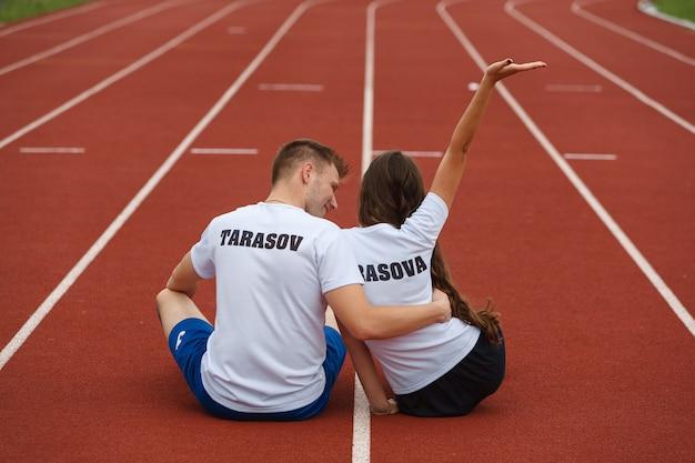 幸せなカップルは、スタジアムでトレッドミル上にあります。スタジアムでジョギングした後の男女。